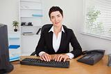 Smiling secretary typing on her keybord
