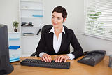 Charming secretary typing on her keybord