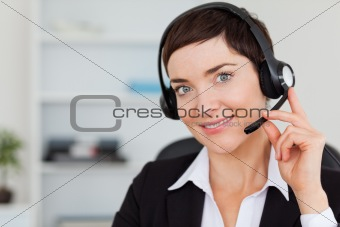 Close up of a smiling secretary calling with a headset