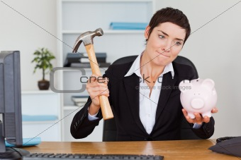 Office worker breaking a piggybank with a hammer