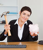 Smiling office worker breaking a piggybank with a hammer