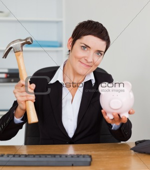 Young office worker breaking a piggybank with a hammer