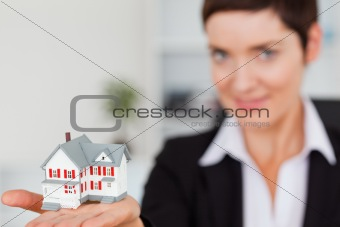 Close up of a brunette showing a house miniature