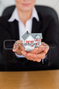 Portrait of feminine hands holding a miniature house