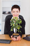Portrait of a businesswoman looking at a plant