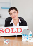 Portrait of a real estate agent with a sold panel and houses min