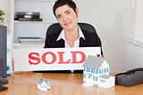 Female real estate agent with a sold panel and houses miniatures