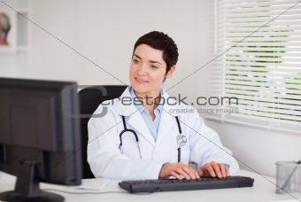 Charming doctor typing with her computer