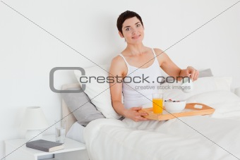 Cute woman pouring milk into her cereal