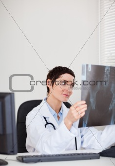 Focused female doctor looking at X-ray