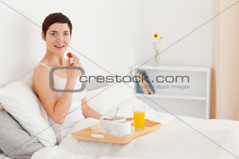 Smiling brunette eating a strawberry