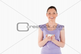 Charming woman enjoying a cup of coffee while standing