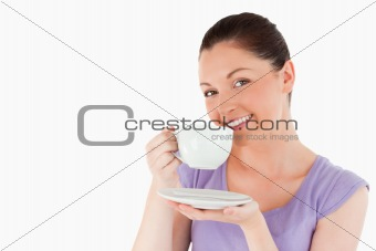 Cute woman enjoying a cup of coffee while standing