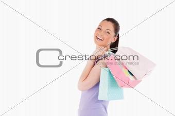 Beautiful woman holding shopping bags while standing