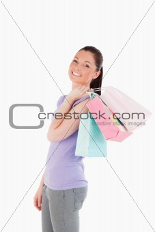 Good looking woman holding shopping bags while standing