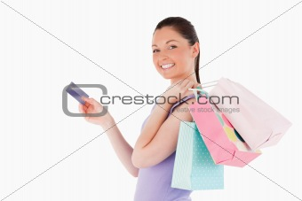 Attractive woman with a credit card holding shopping bags while