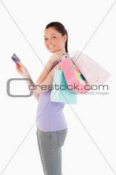 Beautiful woman with a credit card holding shopping bags while s