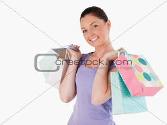 Gorgeous woman holding shopping bags while standing