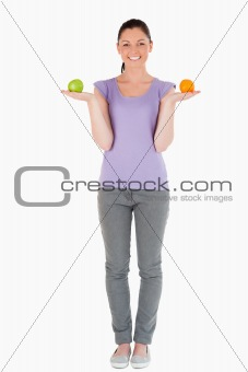 Beautiful woman holding fruits while standing
