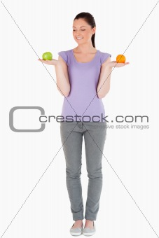 Attractive woman holding fruits while standing