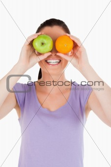 Portrait of an attractive woman playing with fruits while standi