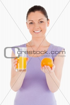 Portrait of an attractive woman holding an orange and a glass of