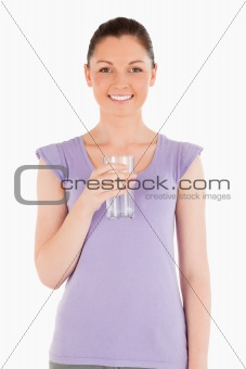 Charming woman holding a glass of water while standing