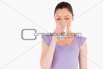 Beautiful woman drinking a glass of water while standing