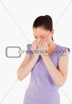 Attractive woman sneezing while standing