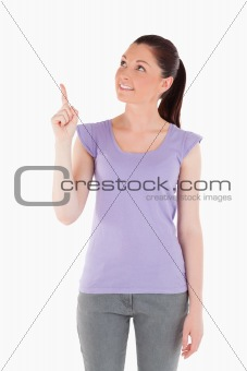 Charming woman pointing at a copy space