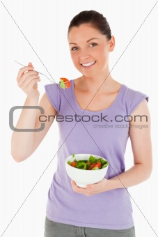 Attractive woman eating a bowl of salad while standing