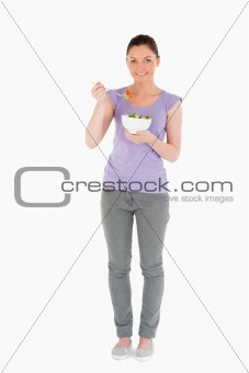 Charming woman eating a bowl of salad while standing