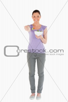 Beautiful woman holding a bowl of salad while standing
