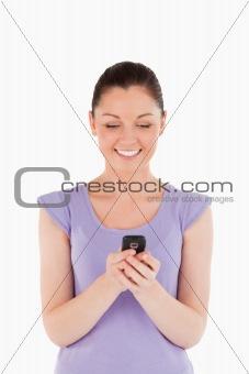 Beautiful woman writing a text on her phone while standing