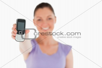 Attractive woman holding and showing her phone while standing