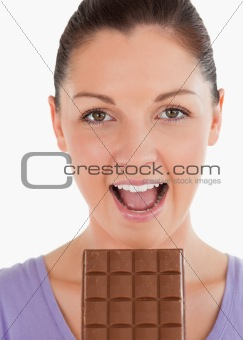 Portrait of an attractive woman eating a chocolate block while s