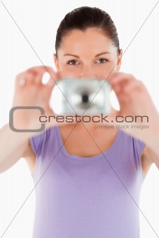 Portrait of a good looking woman using a camera while standing