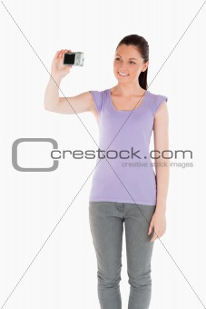Beautiful woman using a camera while standing