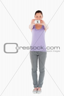 Attractive woman using a camera while standing