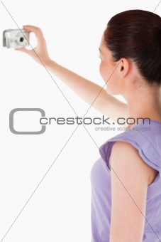 Charming woman using a camera while standing
