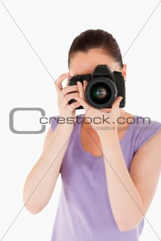 Charming female using a camera while standing