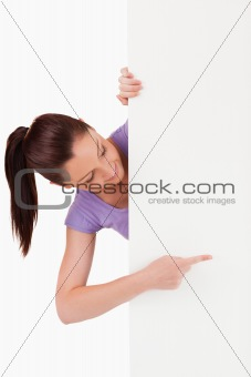 Beautiful female pointing at a copy space while standing