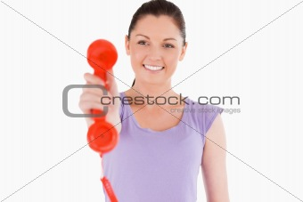 Good looking woman holding a red telephone while standing
