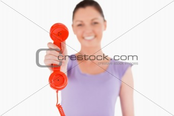 Beautiful woman holding a red telephone while standing