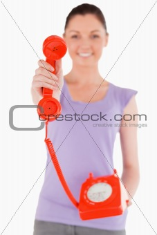 Attractive woman holding a red telephone while standing