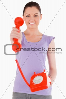 Charming woman holding a red telephone while standing