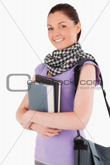 Charming student holding books and her bag while standing