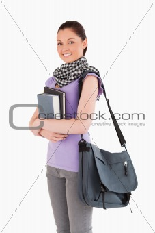 Beautiful student holding books and her bag while standing