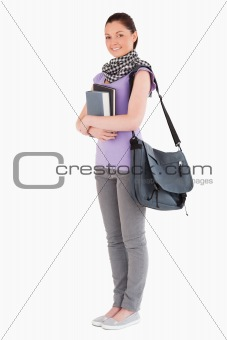 Attractive student holding books and her bag while standing