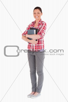 Attractive female posing with books while standing